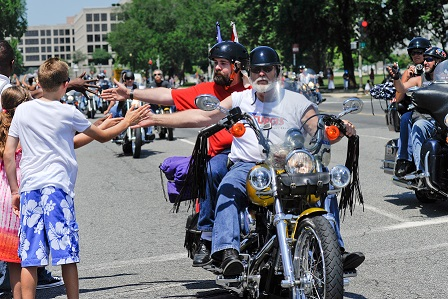 Kids give motorcycle riders a high five